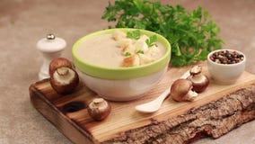 Sopa de champiñones hecha puré sabrosa en cuenco de la arcilla con los ingredientes en tabla de cortar almacen de video