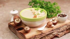 Sopa de champiñones hecha puré sabrosa en cuenco de la arcilla con los ingredientes en tabla de cortar almacen de metraje de vídeo