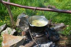 Sopa de cocinar al aire libre en la hoguera Campo que cocina la sopa en la caldera en el fuego abierto Fotografía de archivo