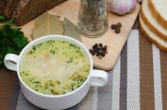 A sopa de cogumelo com pão torrado em um prato branco está em uma tabela de madeira Imagem de Stock Royalty Free