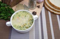 A sopa de cogumelo com pão torrado em um prato branco está em uma tabela de madeira Fotos de Stock