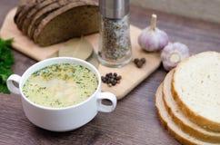 A sopa de cogumelo com pão torrado em um prato branco está em uma tabela de madeira Imagens de Stock Royalty Free