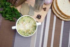 A sopa de cogumelo com pão torrado em um prato branco está em uma tabela de madeira Fotografia de Stock Royalty Free