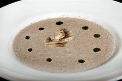Sopa de creme do cogumelo em uma placa branca em um fundo preto Foto de Stock