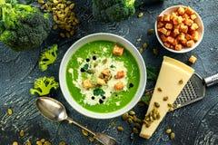 A sopa de creme lisa dos brócolis dietéticos com polvilha de sementes de girassol, de folhas da salsa e de pão torrado na tabela  Foto de Stock Royalty Free