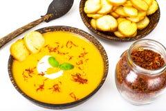 Sopa de creme vegetal com açafrão e pão torrado no backgrou branco Imagens de Stock Royalty Free