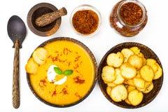 Sopa de creme vegetal com açafrão e pão torrado no backgrou branco Foto de Stock