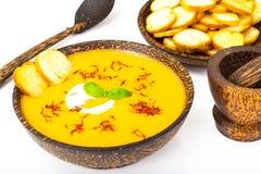 Sopa de creme vegetal com açafrão e pão torrado no backgrou branco Imagens de Stock