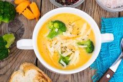 Sopa de creme vegetal com queijo Cheddar e brócolis na tabela de madeira, jantar rural Imagem de Stock