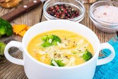 Sopa de creme vegetal com queijo Cheddar e brócolis na tabela de madeira, jantar rural Imagens de Stock