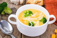 Sopa de creme vegetal com queijo Cheddar e brócolis na tabela de madeira, jantar rural Foto de Stock Royalty Free