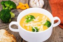 Sopa de creme vegetal com queijo Cheddar e brócolis na tabela de madeira, jantar rural Foto de Stock