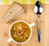 Sopa de ervilha com pão e colher na placa de madeira Imagem de Stock Royalty Free