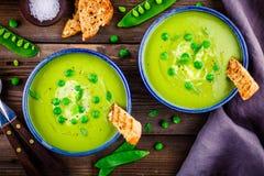 Sopa de ervilha verde no fundo rústico de madeira Imagens de Stock