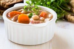 Sopa de feijão branco feita dos feijões, da cenoura e do presunto Fotografia de Stock Royalty Free