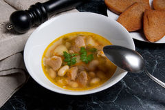 A sopa de feijão na placa branca com colher do metal, diversas brinda no whit Fotos de Stock Royalty Free