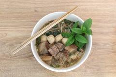 Sopa de fideos asiática del cerdo con la albóndiga y las verduras frescas en el fondo de madera Foto de archivo libre de regalías