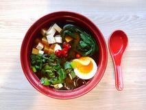 Sopa de fideos del Miso y del soba con el bok choy, el queso de soja, el huevo, la cebolla verde y el chile fotografía de archivo libre de regalías