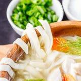 Sopa de fideos hecha en casa del pollo en un cuenco en una tabla de cortar de madera con la coctelera de sal, cebollas verdes taj Foto de archivo
