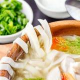 Sopa de fideos hecha en casa del pollo en un cuenco en una tabla de cortar de madera con la coctelera de sal y las cebollas verde Imagen de archivo libre de regalías