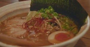 Sopa de fideos japonesa de los ramen - cerdo, huevo, alga marina y caldo hermoso almacen de metraje de vídeo