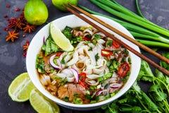 Sopa de fideos vietnamita Pho BO de la carne de vaca con carne de vaca en fondo oscuro Imagen de archivo