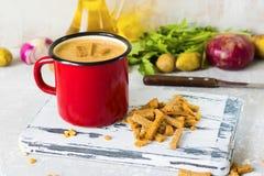 Sopa de guisantes con los purés de patata en taza roja del esmalte imagen de archivo