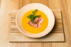 Sopa de guisantes con tocino en una tabla de madera foto de archivo