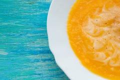 Sopa de la calabaza con crema agria y semillas en una tabla de madera de la turquesa Foco selectivo, aún vida, comida y concepto  Fotografía de archivo libre de regalías