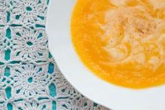 Sopa de la calabaza con crema agria y semillas en una tabla de madera de la turquesa Foco selectivo, aún vida, comida y concepto  Imagen de archivo libre de regalías
