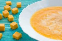 Sopa de la calabaza con crema agria y semillas en una tabla de madera de la turquesa Foco selectivo, aún vida, comida y concepto  Imagen de archivo