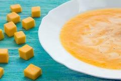 Sopa de la calabaza con crema agria y semillas en una tabla de madera de la turquesa Foco selectivo, aún vida, comida y concepto  Fotos de archivo