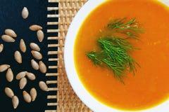 Sopa de la calabaza con eneldo y pan en una estera y las semillas de calabaza Imagen de archivo