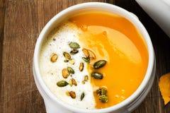 Sopa de la calabaza con las semillas azotadas de la crema y de calabaza en un pla blanco Foto de archivo