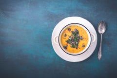 Sopa de la calabaza con las semillas de calabaza y las pimientas de chile fotografía de archivo