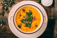 Sopa de la calabaza con las semillas de calabaza y las pimientas de chile foto de archivo libre de regalías