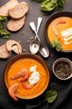 Sopa de la calabaza con los camarones, las semillas amargas, de calabaza en cuencos oscuros y el pan, verdor, cucharas de plata e imagen de archivo libre de regalías