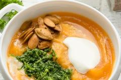 Sopa de la calabaza con pesto y semillas asadas Imagenes de archivo