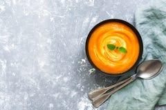 Sopa de la calabaza, cucharas, servilleta en un fondo gris Una copia del espacio, endecha plana Foto de archivo