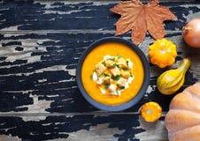 Sopa de la calabaza y de la zanahoria con la crema, cuscurrones, en el fondo oscuro creativo para la acción de gracias, Halloween Imagen de archivo