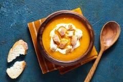 Sopa de la calabaza y de la zanahoria con la crema, galletas en fondo creativo azul Visión superior Comida de la dieta sana Fotos de archivo libres de regalías