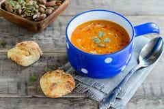 Sopa de la calabaza y de la zanahoria con las nueces y los bollos del pan imagen de archivo libre de regalías
