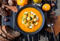 Sopa de la calabaza y de la zanahoria con la crema, cuscurrones en el fondo de madera creativo oscuro para la acción de gracias,  Imagenes de archivo