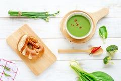 Sopa de la espinaca, pan fresco y verduras verdes en una tabla blanca Imagen de archivo libre de regalías
