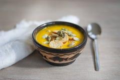 Sopa de la nata de la calabaza en una loza oscura en la tabla de madera Sopa poner crema de la calabaza y de la zanahoria en el f imagen de archivo libre de regalías
