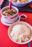 Sopa de las chuletas de cerdo del cerdo con arroz en fondo rojo de la tabla imágenes de archivo libres de regalías