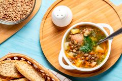 Sopa de lenteja con el pollo en un cuenco blanco en un tablero de madera en una tabla azul, visión superior imagenes de archivo