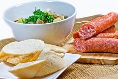 Sopa de lentilha caseiro em uma bacia, em um mettwurst e em um pão brancos com fundo marrom fotografia de stock