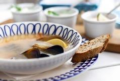 Sopa de los mariscos con los mejillones, las gambas y los pescados en el cuenco blanco con el ornamento azul en restaurante fotos de archivo