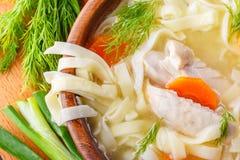 Sopa de macarronete caseiro da galinha em uma bacia em uma placa de corte de madeira com abanador de sal, as cebolas verdes desba Fotografia de Stock
